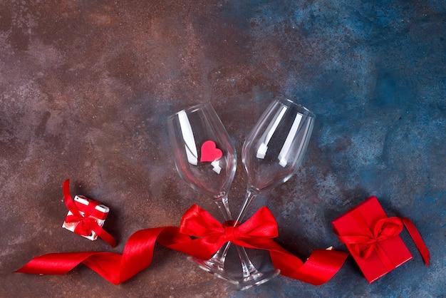 Dois vidros do vinho, dos corações e da caixa de presente no fundo de pedra. dia dos namorados