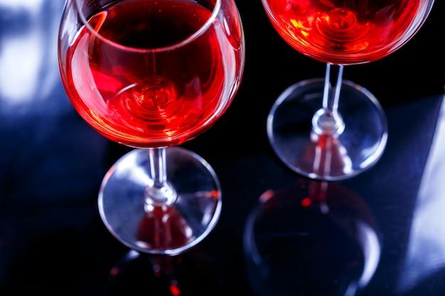 Dois vidros do vinho vermelho na barra, clube nocturno no fundo preto com reflexão.