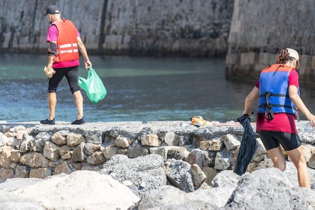 Dois voluntários recolhendo lixo e plásticos no oceano