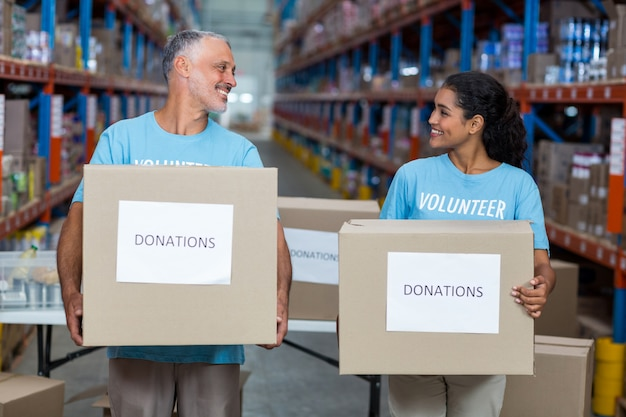 Dois voluntários segurando uma caixa de doações a sorrir