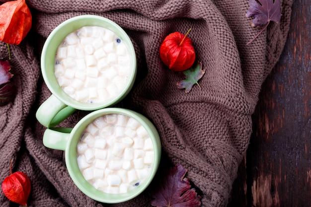 Dois xícara de café ou chocolate quente com marshmallow perto de manta de malha.