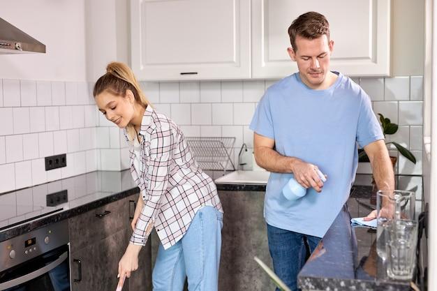 Dois zeladores limpando cozinha e esfregando chão em casa