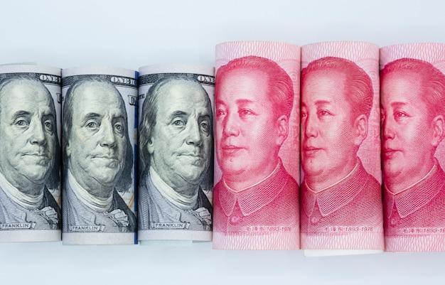 Dólar dos eu e fundo do branco da cédula de china yuan.