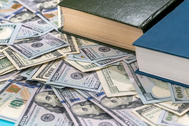 Dólar e livro na superfície azul