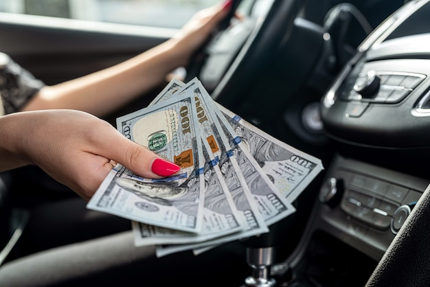 Dólar em mão feminina dentro do carro, close-up