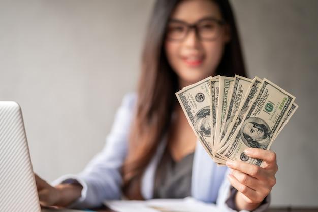Dólar em uma mão de mulher de negócios. uma mulher asiática está trabalhando em casa ou no escritório e feliz em receber dinheiro em dólares do trabalho e de uma carreira suplementar ou trabalho por tempo parcial.