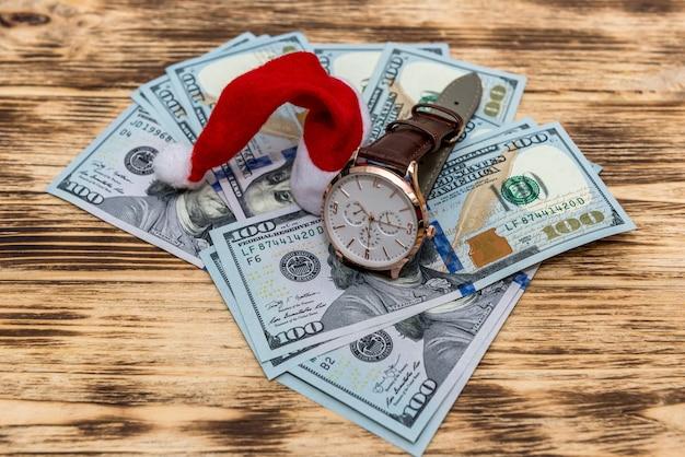 Dólar na mesa de madeira com chapéu de papai noel e relógio