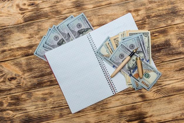 Dólares americanos com bloco de notas vazio e caneta