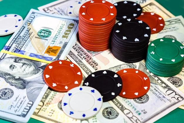 Dólares americanos do dinheiro e microplaquetas de pôquer no fim da tabela do casino acima.