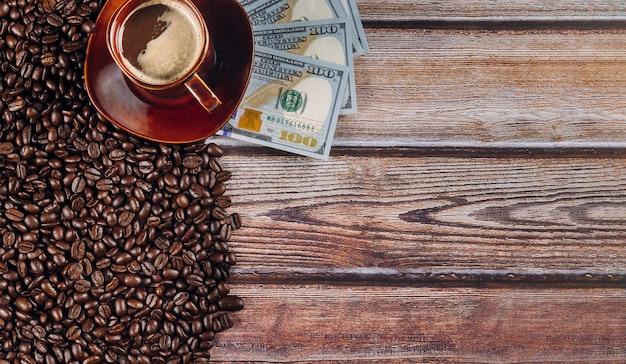 Dólares americanos e grãos de café e xícara de café na mesa de madeira.