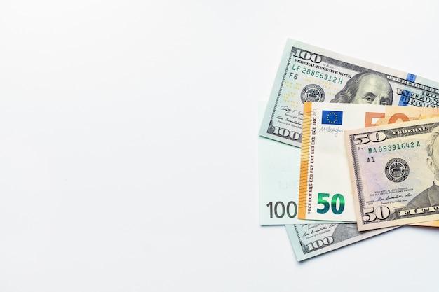 Dólares americanos e notas de euro em fundo branco