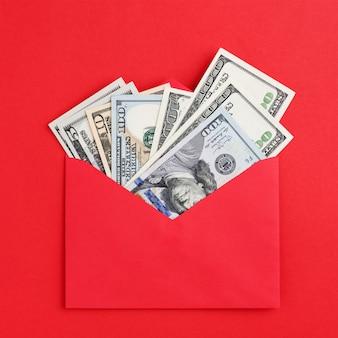 Dólares americanos em envelope vermelho e mesa