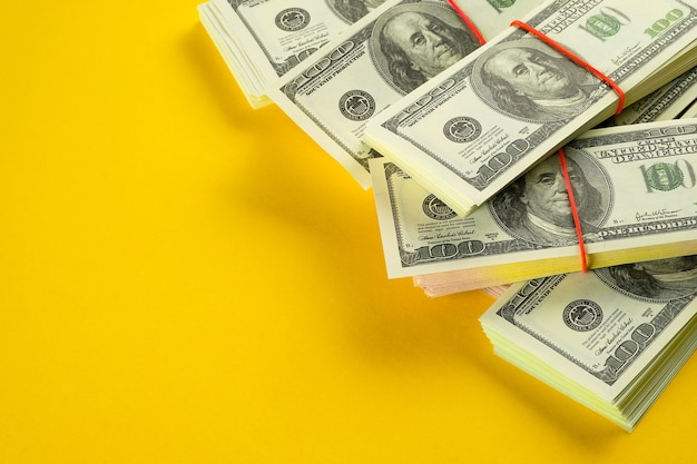 Dólares americanos em pacotes em um amarelo brilhante