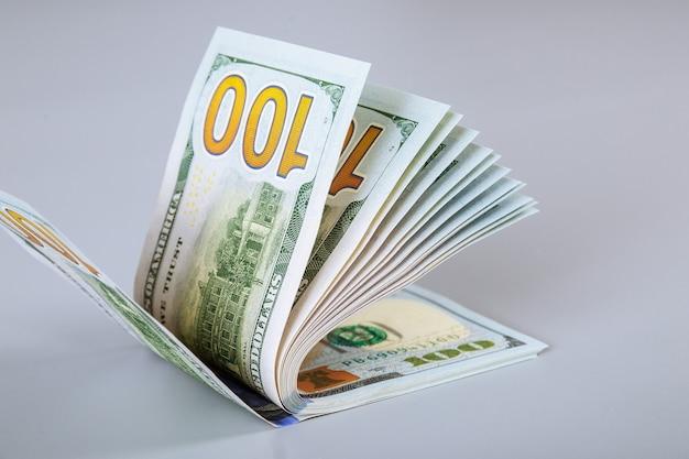Dólares americanos em uma mesa cinza. conta com notas de cem dólares.