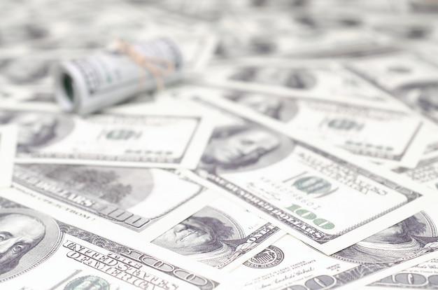 Dólares americanos enrolados e apertados com mentiras de banda em um monte de notas americanas