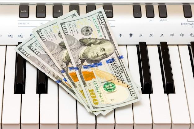 Dólares americanos estão nas teclas do piano. pagamento pelo concerto, lucro com a execução de obras musicais