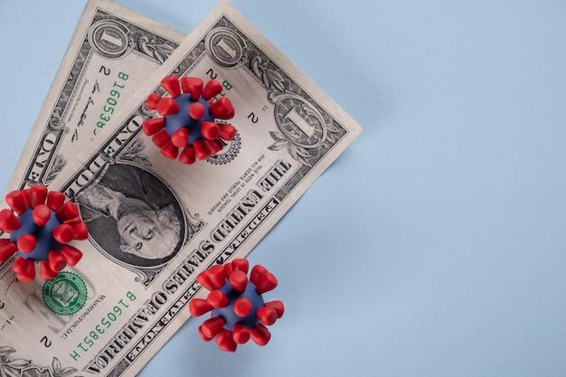 Dólares americanos, moedas e modelos de vírus covid-19 contaminados infectados em dinheiro. crise econômica