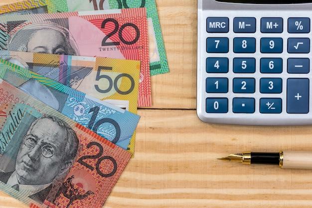 Dólares australianos, caneta e calculadora em fundo de madeira