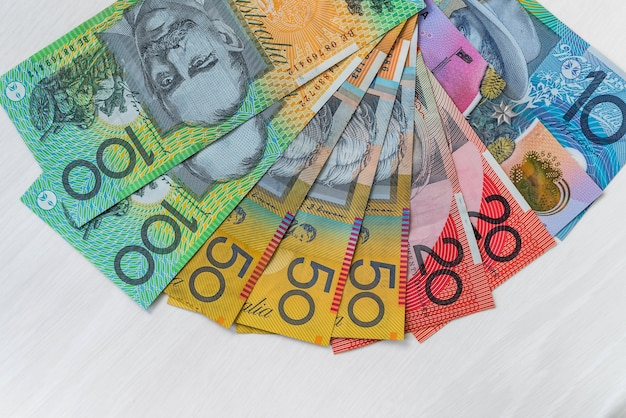 Dólares australianos coloridos na mesa de madeira