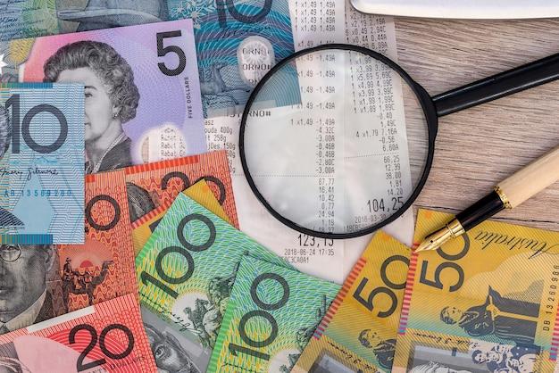 Dólares australianos com recibo, calculadora, caneta e lupa
