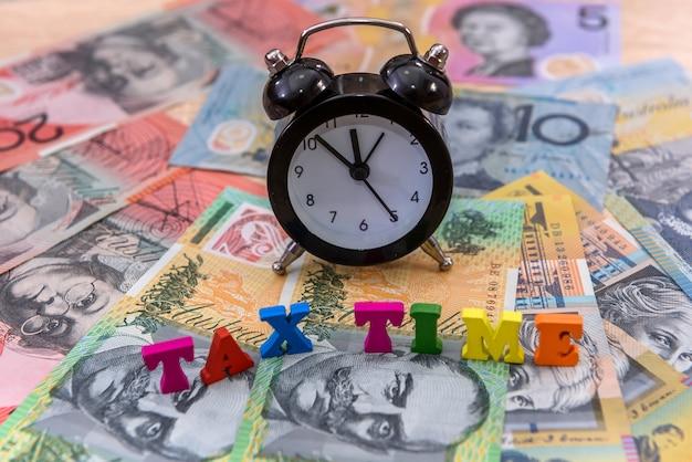 Dólares australianos com relógio e texto 'hora do imposto'