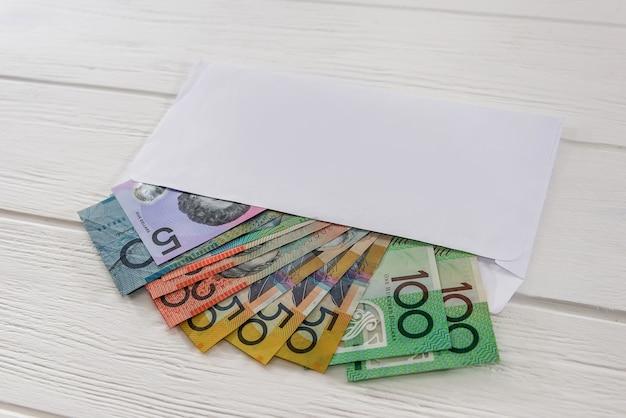 Dólares australianos em envelope na mesa de madeira