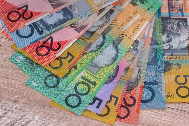 Dólares australianos em leque em mesa de madeira