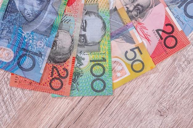 Dólares australianos em leque na mesa de madeira