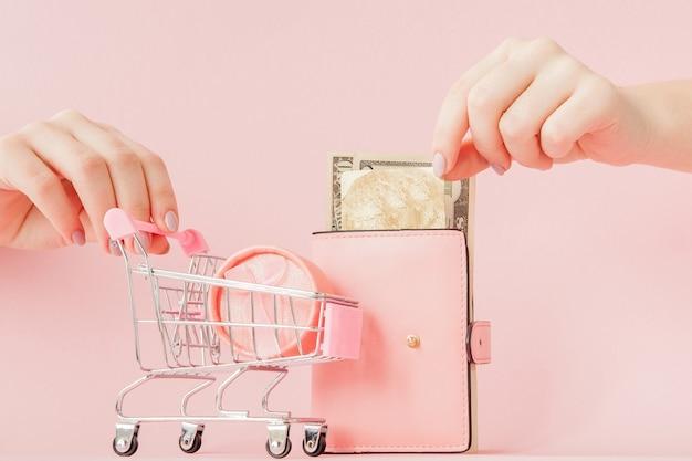 Dólares, caixa de presente e carteira rosa com cartão de crédito nas mãos de mulher rosa