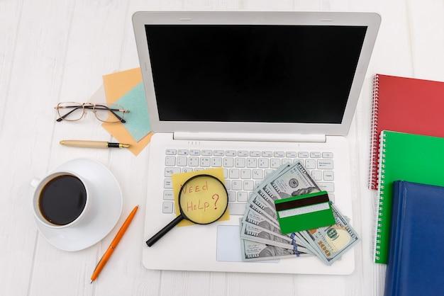 Dólares com cartão de crédito e lupa no teclado do laptop