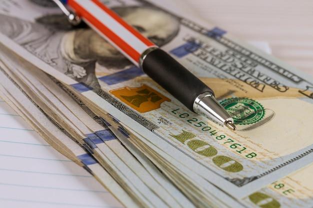 Dólares de cem contas em dinheiro com uma caneta