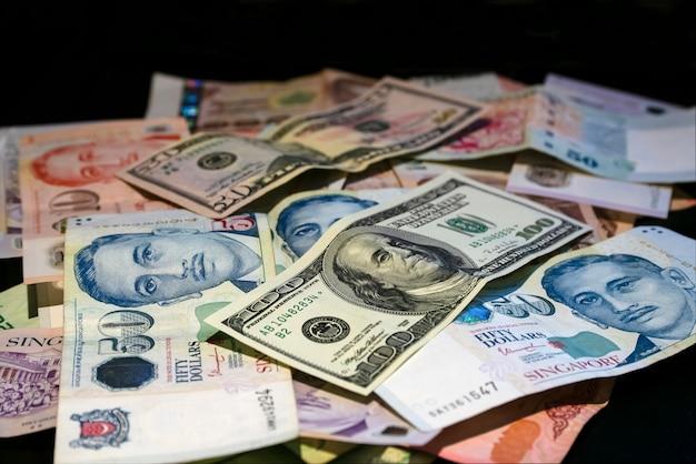 Dólares de cingapura em dinheiro e dólares americanos estão na mesa misturados.