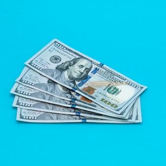 Dólares de contas de dinheiro em um fundo azul.