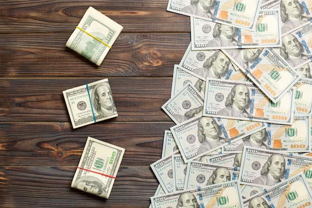 Dólares de moeda na vista superior colorida, com dinheiro do negócio de lugar vazio. notas de cem dólares com pilha de dinheiro