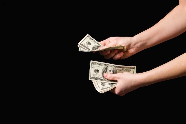Dólares do dinheiro nas mãos no fundo escuro