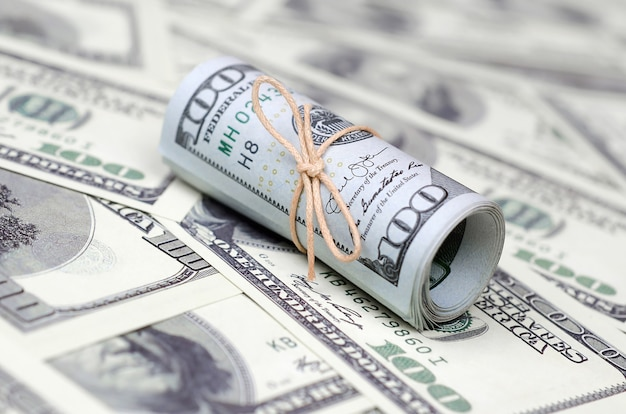Dólares dos eua enrolados e apertados com banda estão em muitas notas americanas com fundo desfocado