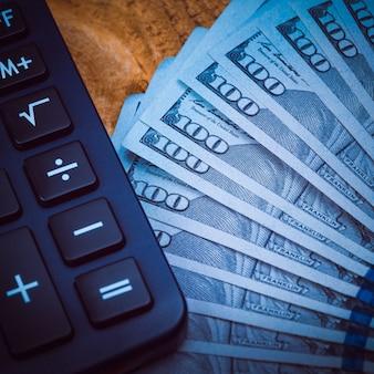 Dólares e calculadora em pranchas de madeira. luz azul escuro, vinhetas.