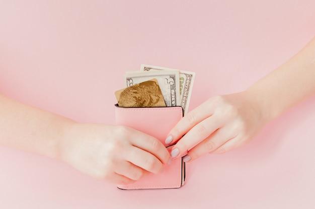 Dólares e carteira rosa com cartão de crédito em mãos femininas
