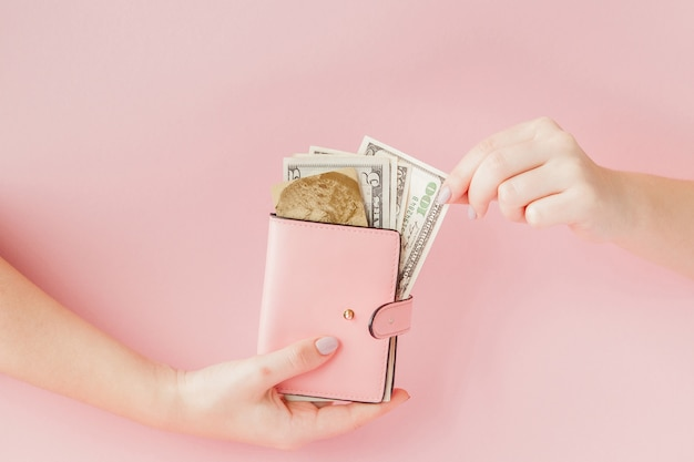 Dólares e carteira rosa com cartão de crédito nas mãos da mulher