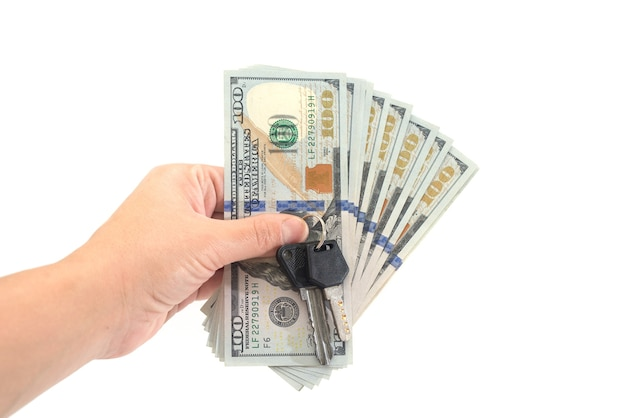 Dólares e chaves em mãos. isolado no branco.