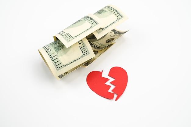 Dólares e coração partido, sobre um fundo branco isolado. foto de alta qualidade