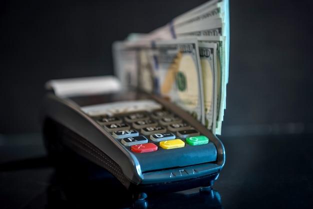 Dólares e terminal bancário com cartão de crédito