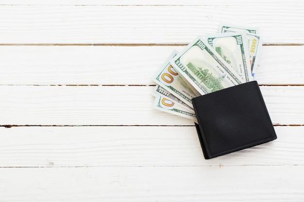 Dólares em carteira preta em fundo branco de madeira