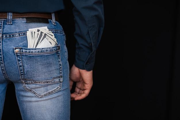 Dólares em dinheiro e um preservativo no bolso de trás dos jeans masculinos