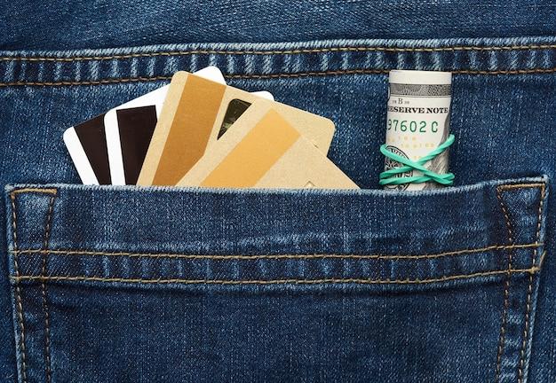 Dólares em papel enrolado e cartões bancários de plástico