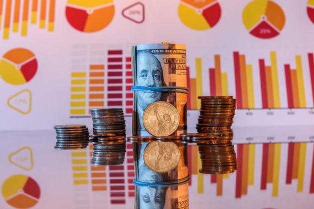 Dólares em rolo e moedas na superfície brilhante