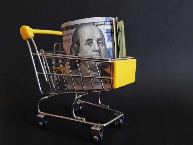 Dólares em um carrinho de brinquedo em um fundo preto isolado