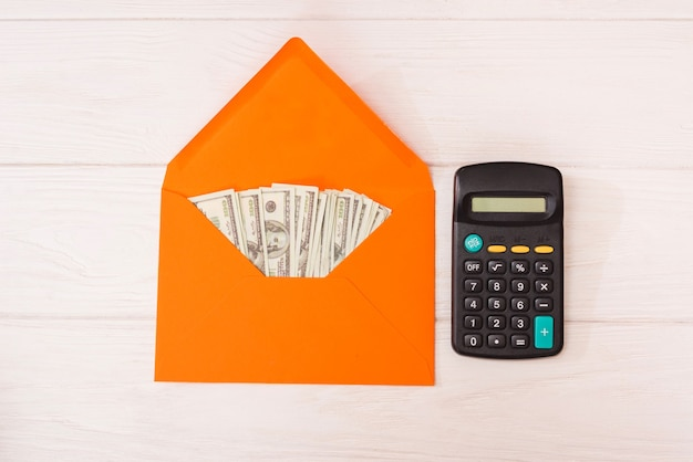 Dólares em um envelope laranja e uma calculadora em um fundo branco de madeira.