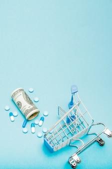 Dólares, pílulas e carrinho de compras em uma mesa azul. conceito de farmácia. copie o espaço