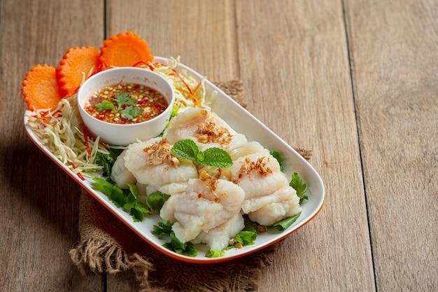 Dolly peixe cozido com molho picante de frutos do mar.